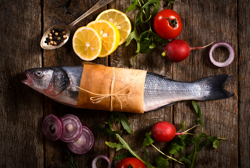 Raw Bass Fish With Vegetables From Above On The Wooden Background